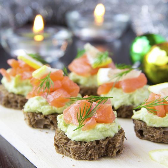 Appetizer canapes of bread with avocado and red fish for Canape appetizers