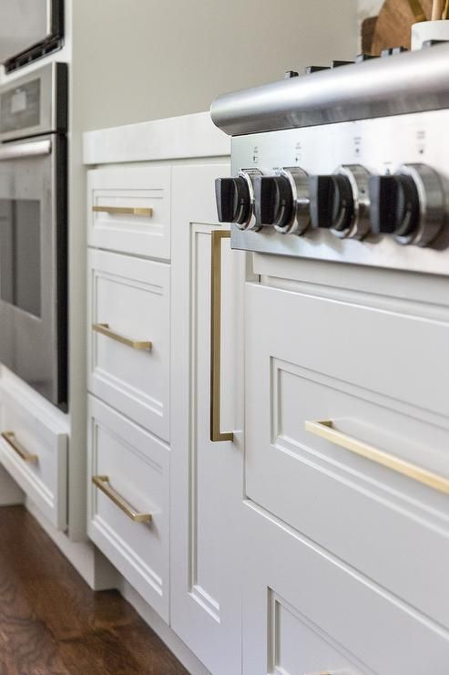 Long Thin Brass Pulls On White Kitchen Cabinets Brings A Warm Glowing Appeal To The Fresh White Doors White Marble Countertops Light Grey Kitchens White Doors