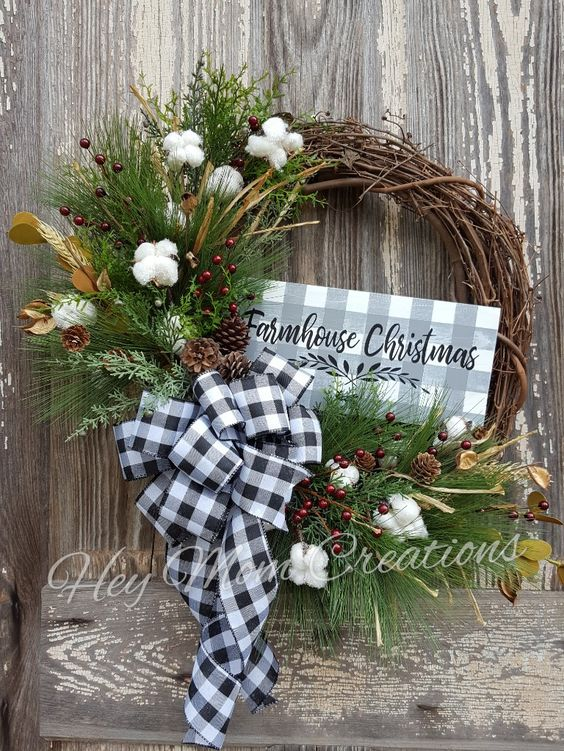 "This wreath would be the perfect addition to your Farmhouse Christmas decor. Made on an 18"" grapevine base with pine greenery stems, pine cones, dark red berry stems, white glittered cotton bolls, also has a hand painted grey buffalo plaid farmhouse Christmas wood sign with an ever so popular black and white buffalo plaid bow. Ready to ship! Approximate diameter: 22"" tip to tip"