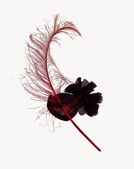 Tocado Tamashii by nila taranco. Una base de rafia negra con una gran pluma de avestruz quemado en rojo adornado por una flor de seda también en negro en un lateral.