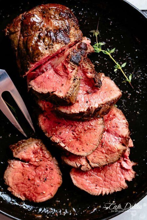 The best, juicy roast Beef Tenderloin slathered with garlic butter in a skillet #cafedelites #beef #tenderloin #steak #Christmas #dinner