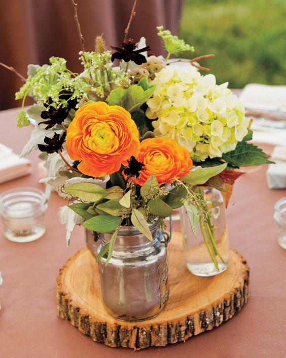 Ranunculus, hydrangeas, and Queen Anne's lace atop hand-cut oak rounds create a woodsy, autumnal palette.