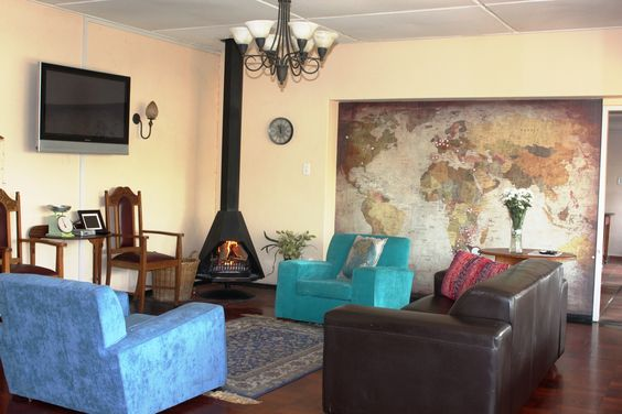 World map wallpaper. Beautiful lounge with fireplace. Blue chair. Wooden floors. Book now at 3@Marion guesthouse. Pretoria. Tshwane