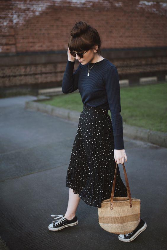 Look saia midi plissada com estampa de poá, suéter e all star preto.