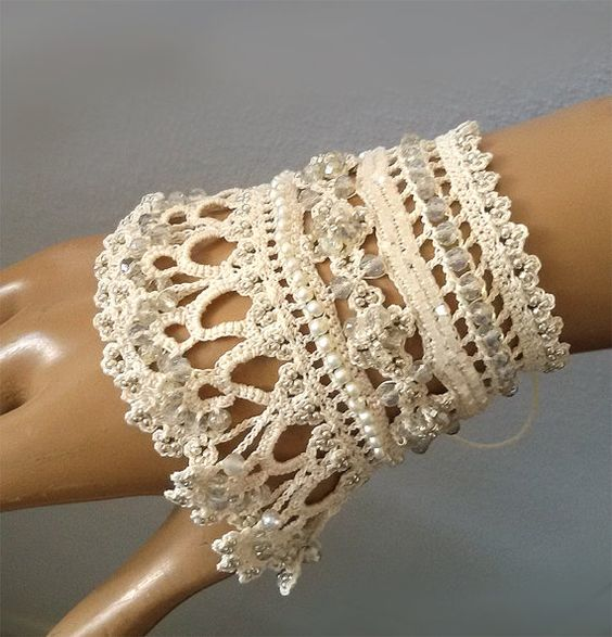 The cuff bracelet is created with light beads, beige 100% cotton, embellished with beads and hand crocheted lace.  --------------------------------------------------------------------------------------  --------------------------------------------------------------------------------------  The bracelet has a unique design, its base is composed of openwork lace crocheted with beige cotton fiber. And I used two shades of beaded crochet flowers and natural forms in ornament cuff. I added a beige...:
