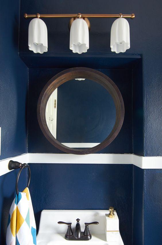 Gold vanity light with dark blue walls