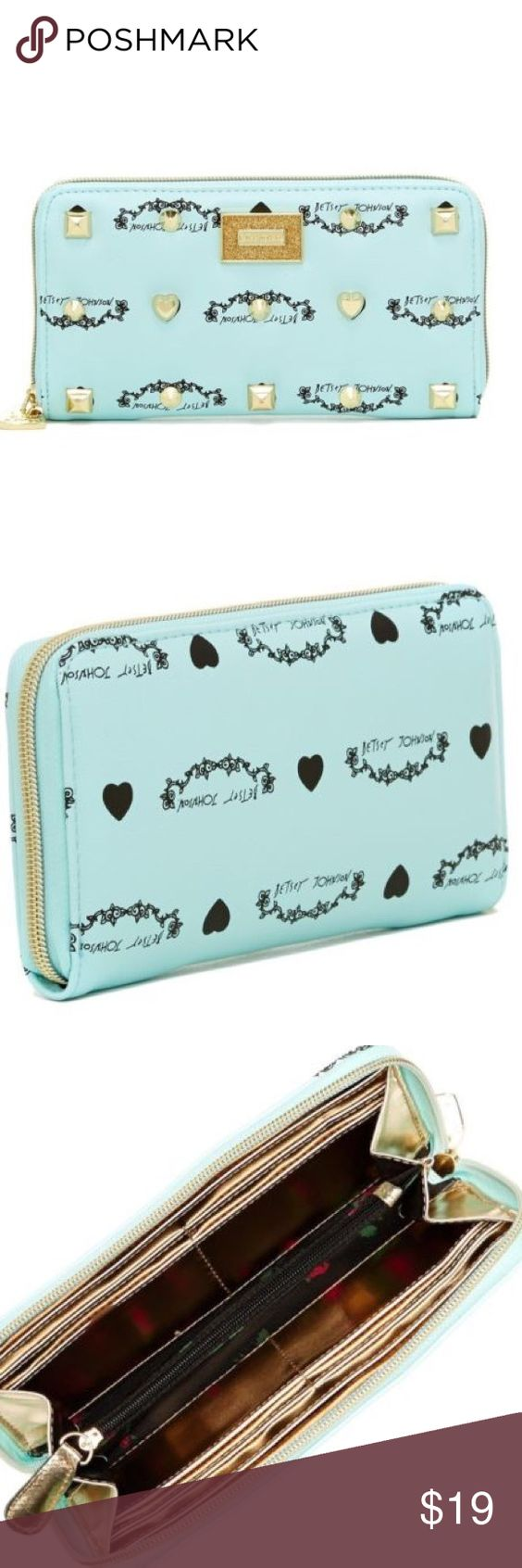 Betsey Johnson Signature Wallet Betsey Johnson signature logo covers the light blue faux leather outside of this wallet, as well as gold toned studs. Front outer wall with logo plaque. Open the zip-around closure to the polyester lined inside featuring rose pattern and you'll see 8 credit card slots, 2 full length bill pouches, a clear ID slot and a large zip coin compartment. Nice basic wallet. Betsey Johnson Bags Wallets