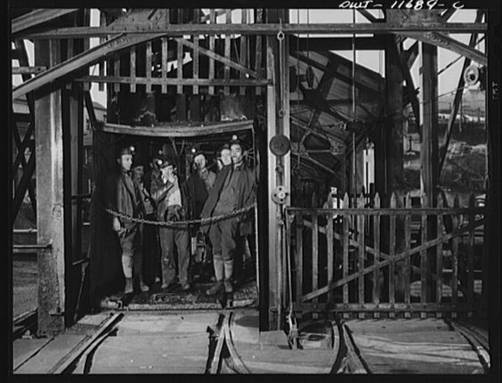 Miners about to be lowered into a dfep pit coal mine cage. .jpg (1024×781)