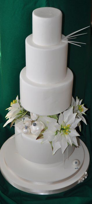 Unique white wedding cake with flowers in between the layers.  Lovely!