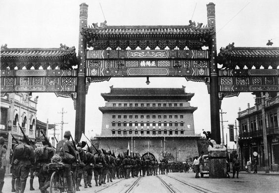 First pictures of the Japanese occupation of Peiping (Beijing) in China, on August 13, 1937. Under the banner of the rising sun, Japanese troops are shown passing from the Chinese City of Peiping into the Tartar City through Chen-men, the main gate leading onward to the palaces in the Forbidden City.
