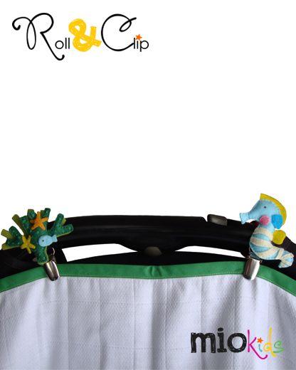 Par de braçadeiras e Mio Personagens Roll & Clip segurando uma fralda numa alcofa. | Pair of Roll & Clip Mio Characters and bands, securing a nappy in a carrycot arm.