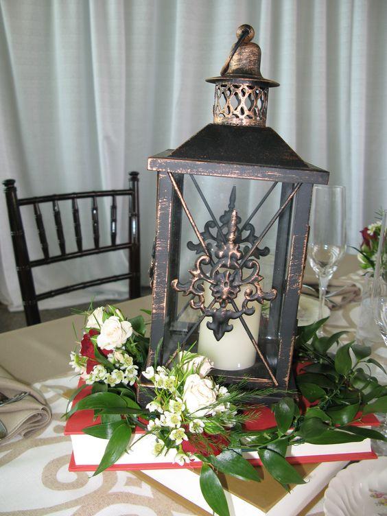 Metal lantern with greenery ring set on books.