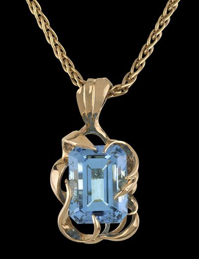 """""""Ensenada"""". Blue topaz set in gold pendant. Designed by Teri Wallace of Mineral Search, Inc. Irradiation—bombarding a gem with gamma rays—and heat treatment are two ways to enhance the color of stones. Both are common and widely accepted practices in the gem trade. Note that the stone in this pendant, which has been treated, is a much deeper blue than the """"Chalmers Topaz."""""""