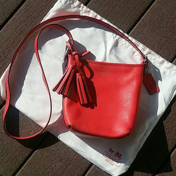 Small coach bucket bag Bright coral crossbody bucket bag. Tassel detail. Silver hardware.  Very gently loved, great condition. Coach Bags Crossbody Bags