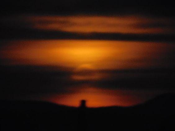Der Mond scheint in rötlich-orangen Farben am Horizont.