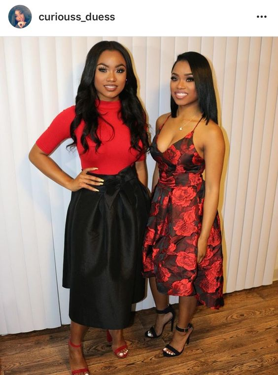 Beautiful twins 3/4 sleeve blouse black a line midi skirt red ankle strap heels long  curly hair red lips red and black floral midi dress long straight hair black ankle strap heels