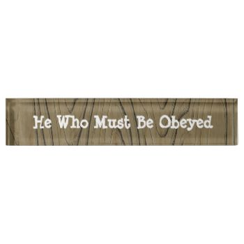 """A fun desk sign makes an ideal novelty gift for a family member, co worker or boss, in a wood grain effect and white writing. Feel free to change the words, """"He Who Must Be Obeyed"""" to suit your needs."""