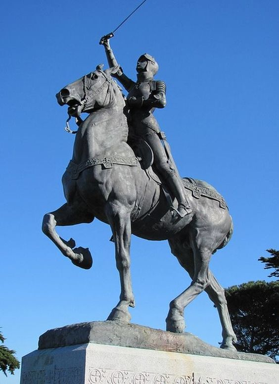 """Anna Vaughn Hyatt Huntington (American sculptor) 1876 - 1973 Joan of Arc, 1915 bronze, Mohegan granite 20'4"""" x 6'1"""" x 12' inscription: JOAN OF ARC / BORN AT / DOMREMY FRANCE / JANUARY 6TH,1411 / BURNED AT THE STAKE AT / ROUEN, FRANCE / MAY 30TH, 1431/ ERECTED BY / THE JOAN OF ARC STATUE COMMITTEE / IN THE CITY OF NEW YORK 1915."""
