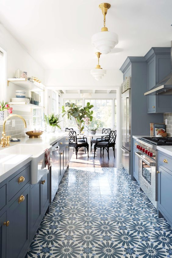 Emily Henderson beautiful slate blue galley style kitchen with cement tiles, open shelving, farm sink, brass hardware and fittings, and Wolf range. #classic #kitchen #bluekitchen #cementtile