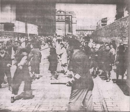 Warsaw, Poland, A Jewish policeman dispersing a crowd of children in the ghetto