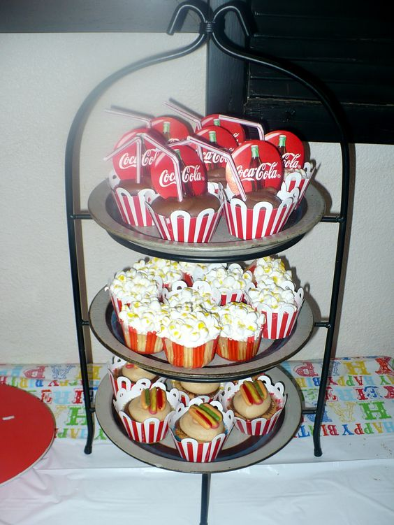 Carnival Themed cupcakes. Top are coca-cola flavored cupcakes, middle-butter flavored decorated to look like popcorn (marshellows) and bottom-peanutbutter cup cup cakes with hot dog gummy decorations.
