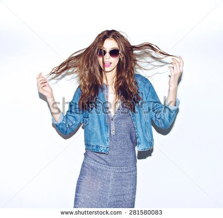 Emotional pretty young hipster girl in sunglasses make funny face and keep hairs in hand on blue background  - stock photo