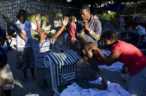 Offering  A group of Haitians pray as a woman is treated at the Villa Creole Hotel.