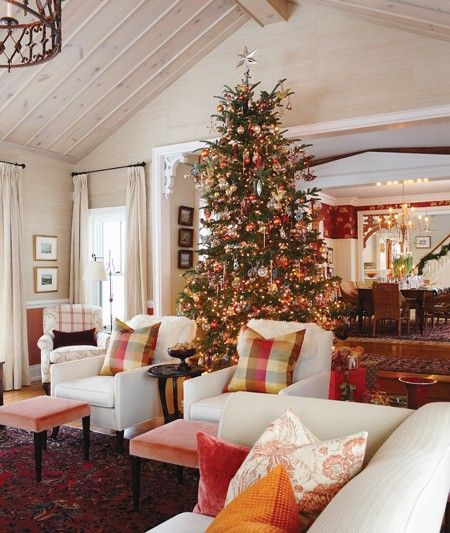 The 12-foot tree in designer and HGTV host Sarah Richardson's farmhouse living room was cut down on their property by Sarah's husband. Loaded with ornaments, both old and new, the tree stands between the dining room and living room, allowing it to be seen from many vantage points. The warm colour scheme of red, orange and cream in the space creates a cozy feeling, perfect for a country home.
