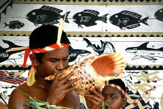 Palau traditional male dancer blowing a conch in front of a Abai