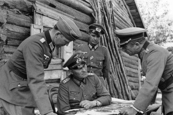 General Oberst Erich Hoepner (1886-1944, sitting center) confers with the commander of the 6th Armored Division, Major General Franz Landgraf (1888-1944, right) and staff officers in a village house near Leningrad, August 1941.
