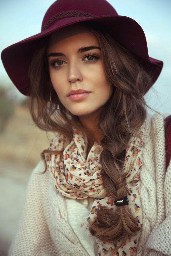 woman wearing a burgundy wool floppy hat with light brown hair in a side braid, floral scarf and warm cream colored sweater