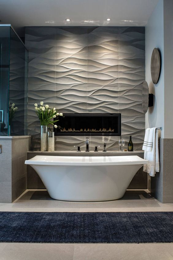 Bathroom Tile Idea - Install 3D Tiles To Add Texture To Your Bathroom | Wavy tiles behind the bathtub and surrounding the built in fireplace create a feature wall that can also double as art.
