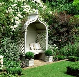 A gothic covered seat with cushions in  formal garden. Rosa 'Kiftsgate', Teucrinum, Cotinus etc.