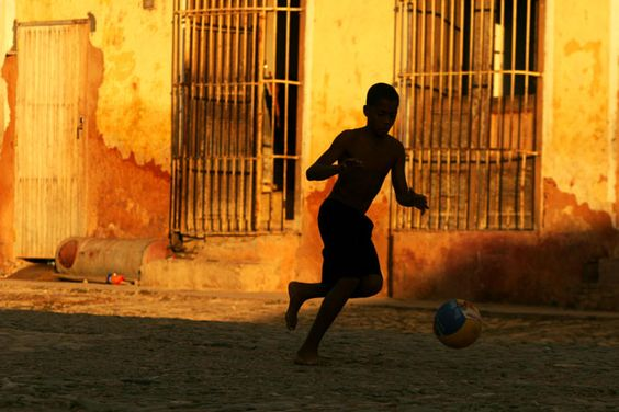 Boy playing football in Havana streets