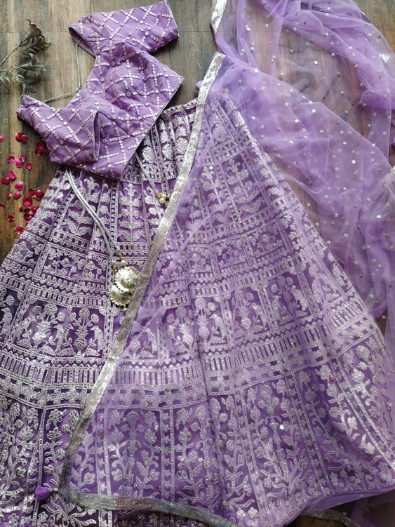 BLOUSE - Mirror-work Blouse Sweetheart neckline with Silver piping detail Back Open design with handmade tassel tie-up Blouse is stitched and padded LEHENGA - Lilac kalidar Lehenga with Foil work Gota Tassels on waist tie-up Can can layering inside DUPATTA - Sequinned bootis Net Dupatta Handmade Gota tassels on the edges Silver sequins border on all edges