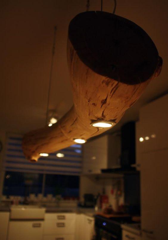 Boomstamlamp boven eettafel. Hangt aan staaldraad en is voorzien van spotjes.