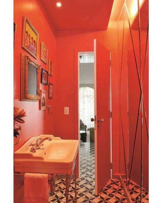 Com quadros criados  pelos moradores com referências da juventude, o lavabo assinado pelo designer Marcelo Rosenbaum tem paredes e teto pintado. A luz da sanca banha a parede revestida de espelho com recortes bisotados. Foto Marcelo Magnani/Editora Globo @marcelorosenbaum #banheiro #bathroom #espelhos #mirror #quadros #lavabo