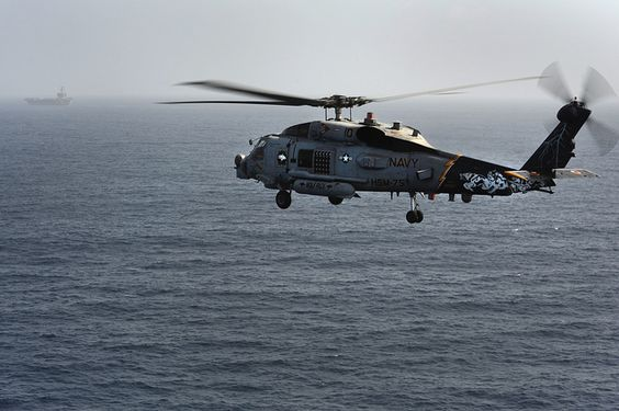 """GULF OF OMAN (June 21, 2013) An MH-60R Sea Hawk helicopter assigned to the """"Wolf Pack"""" of Helicopter Maritime Strike Squadron (HSM) 75 approaches the aircraft carrier USS Nimitz (CVN 68). Nimitz Strike Group is deployed to the U.S. 5th Fleet area of responsibility conducting maritime security operations, theater security cooperation efforts and support missions for Operation Enduring Freedom."""