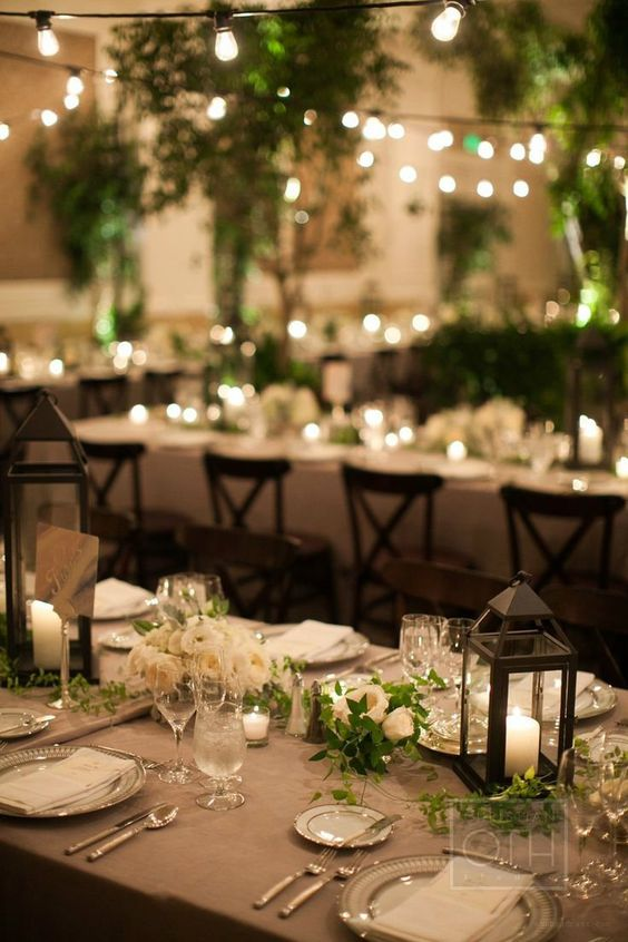 An indoor garden with potted trees, ferns, downtown abbey inspired arrangements with lanterns and lights throughout.: