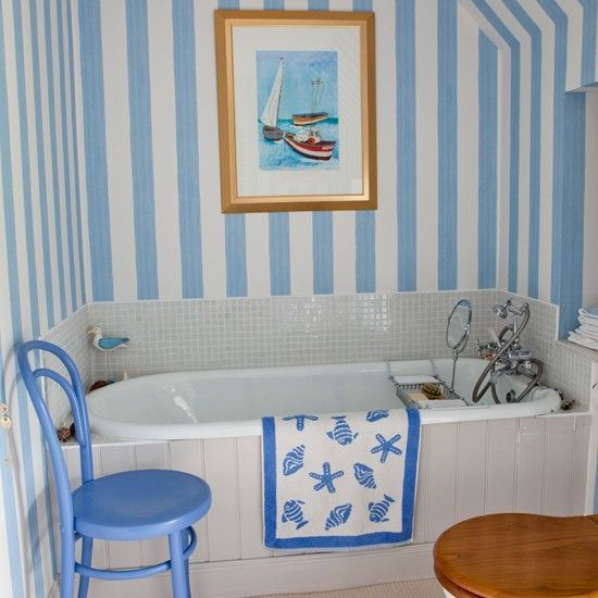 Blue and white stripes add a fresh coastal feel to this bathroom, making the most of a small space.