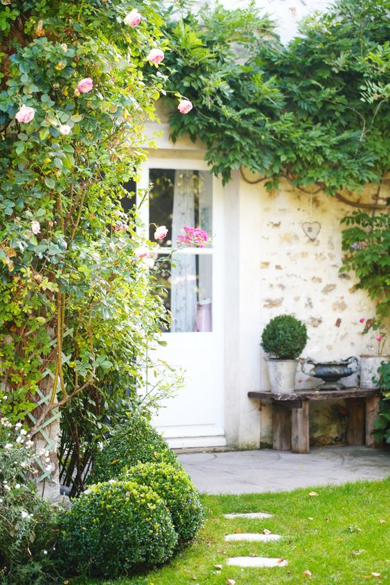 French farmhouse exterior with rustic bench and climbing vines via Grange de Charme. #frenchfarmhouse #cottagestyle #garden