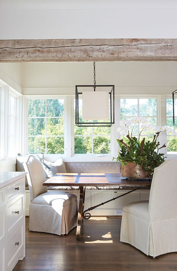 "Banquette. A favorite gathering spot in this house is a built-in banquette in the kitchen. ""The table really set the stage for the entire house,"" Jan says. ""We built so much of the rest of the house around it."" Large enough to seat at least 10, the table is an antique French piece with iron strapping. To counterbalance the table's size, Jan chose to include it in a breakfast nook and add upholstered banquette seating around it. DESIGNER: Jan Ware:"