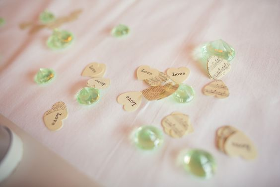 Table crystals and confetti. The 'vintage books' confetti was to represent my husband as he's an avid reader and, as a musician, the vintage music script was for me. We also had paper roses in my bouquet and some of the pew ends on the same theme.
