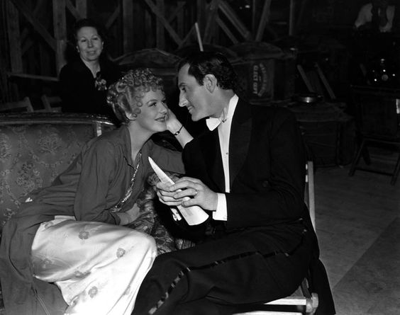 A candid shot of Rathbone and Veda Ann Borg on the set of Confession.:
