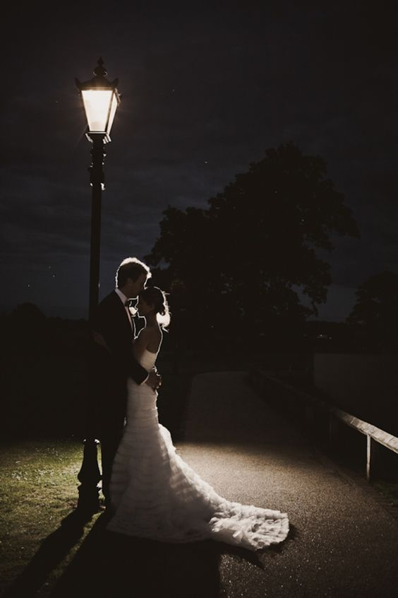 Bride and groom under a street lamp at night