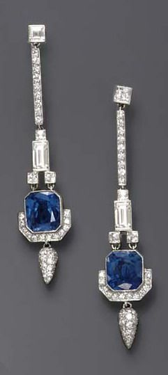 Art Deco Diamond And Sapphire Ear Pendants~ Each square-cut diamond, suspending a circular-cut diamond line, to the square and baguette-cut diamond link, terminating in a rectangular-cut sapphire, weighing approximately 4.91 and 4.59 carats, enhanced by circular-cut diamond trim and a pavé-set diamond drop, mounted in platinum, in a red leather case.