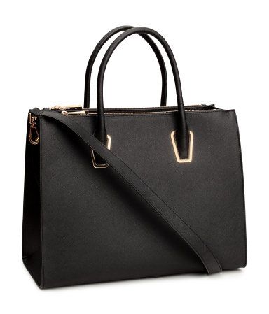 Handbag in sturdy grained imitation leather with two handles and a detachable shoulder strap at the top, one large compartment and two zipped compartments along the long sides, three inner compartments, one with a zip, and studs on the bottom. Size 28x38 cm.