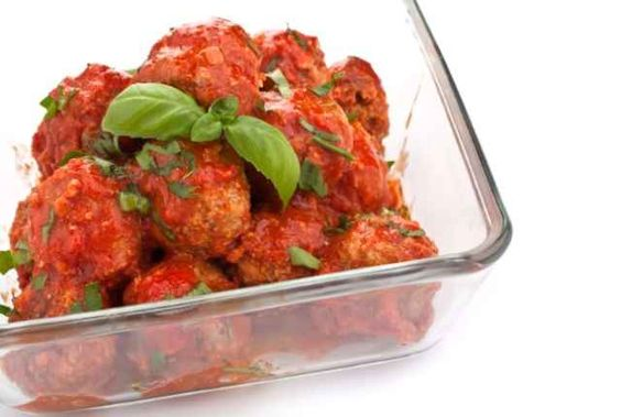 big bowl of meatballs in tomato sauce and basil