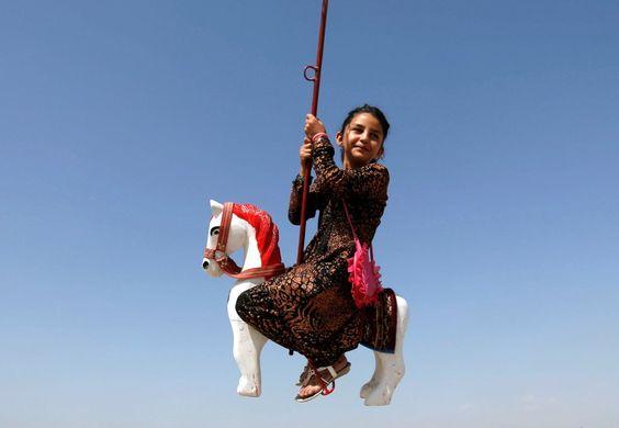 Una niña afgana monta en una atracción de feria durante el primer día de la…