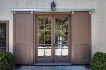 External trolley doors using sleek track and flanked by rounded boxwood. BellaRusticaDesign.com